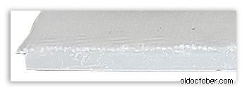 Торцевая часть шильдика на границе с тканью.