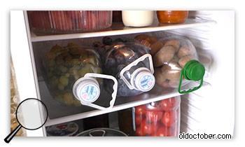 Три контейнера между полками холодильника.